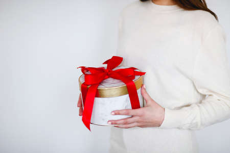 Unrecognizable girl in white sweater holding round present box tied with bright red ribbon during holiday celebration