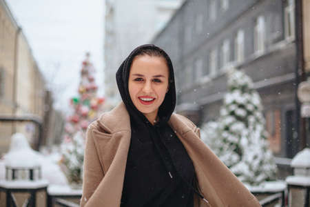 Young positive woman with funny smile on her face stands outside in beige coat and black scarf on head, shivering from winter cold weather against background of trees covered with thick layer of snow Stockfoto