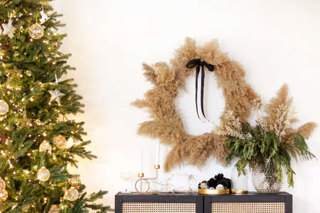 Assorted stylish decorations placed on shelf and wall near Christmas tree with bright fairy lights and stylish baubles at home