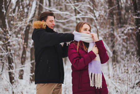 Photo of beautiful young teen couple spending time together outside in cold winter, guy straightening knitted girls scarf to keep her warm on frosty day. Romantic date outdoors