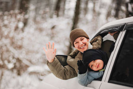 Cheerful adult woman and little boy in outerwear looking at camera and waving hands while peeking out from vehicle window on blurred background of winter forest Stockfoto