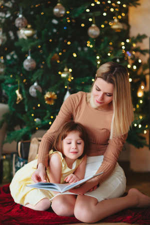 Happy family grandmother and little girl daughter sitting together on sofa and reading book while spending time together at home during Christmas holidays in winter, hugging and covering with wool plaid