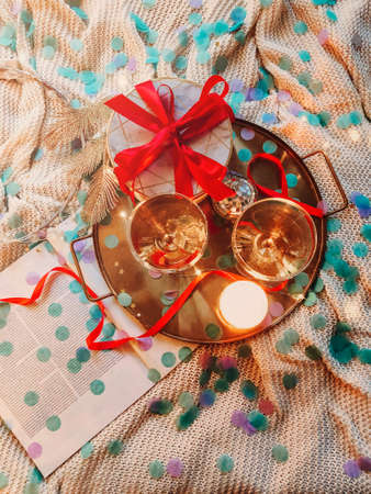 Tray with decorations and gift box placed on comfortable bed in cozy bedroom decorated for Christmas celebration at night