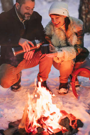 Joyful happy family couple in love basking by campfire outside in winter snowy forest drinking hot tea together, man and woman warm themselves hugging and loving look at each other. Trekking, adventure and seasonal vacation