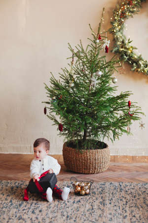 Cute little boy toddler sitting on carpet under decorated christmas tree and unwrapping black gift box with red ribbon during winter holiday season, wearing white buttoned sweater with plaid pants