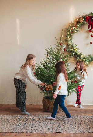 Happy four little siblings, three sisters in warm knitted sweaters gathered around fir-tree in living room and decorating it with toys and glossy balls. Family and christmas concept