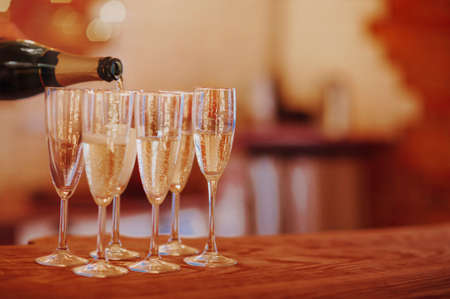 Unrecognizable male filling wineglass with champagne while standing on banquet table with burning candles during Christmas party at home Stockfoto
