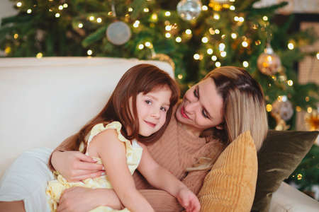 Happy playful little girl daughter playing with positive mother, spending time together during Christmas holidays at home, mom and child having fun in living room with New Year tree