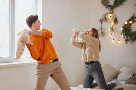 Happy young lovely couple having fun, fighting with pillows on bed in New Years festively decorated bedroom, two teenagers enjoying company of each other, spending time at home during Christmas Stockfoto