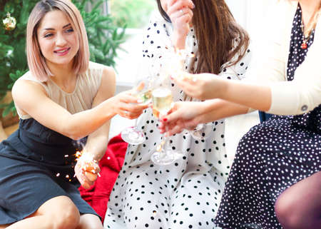 Cheerful female with sparkler smiling and clinking glasses with crop friends during Christmas party at home