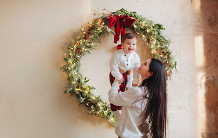 Young woman smiling and playing with cute boy on blurred background of decorated coniferous tree on Christmas day at home