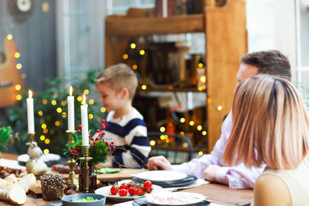 Adult man in glasses hugging happy son and wife while sitting at dining table in cozy room at home during holiday celebration Stockfoto