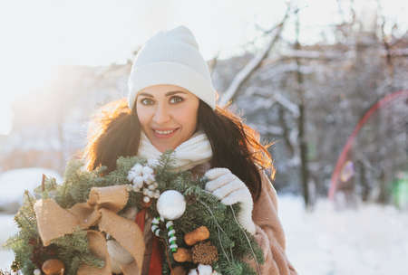 Happy female in outerwear carrying decorated Christmas wreath and standing on snow on sunny winter day