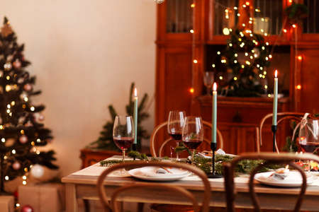 Burning candles and glasses of red wine placed near plates and coniferous branches during Christmas celebration at home