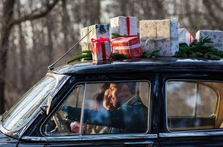 Loving man and woman hugging in retro car with Christmas gifts on roof in park