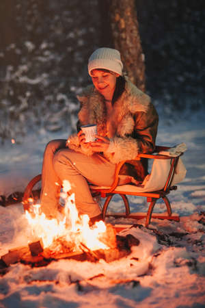 Happy young woman full of calmness and pacification in warm knitted hat and jacket sits on wooden sled by bonfire with cup of hot tea in her hands, surrounded by night snow-covered winter forest
