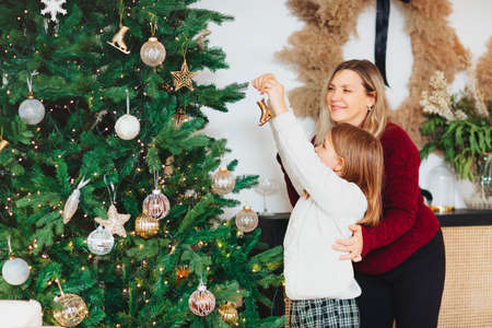 Joyful mother and lovely girl daughter in cozy knitted sweaters decorating Christmasmas fir tree with new year baubles and toys in living room, smile feeling atmosphere of winter holiday. Family holidays Stockfoto