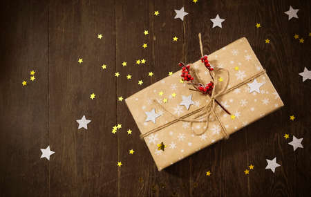 Top view of stylish gift box decorated with berries and stars placed on wooden tabletop during Christmas celebration
