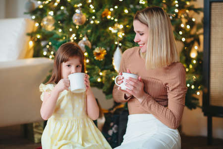 Happy family, mother and little daughter drinking hot cacao, sitting near decorated? Hristmas tree, mom and child spending time together at home during winter holidays, celebrating New Year
