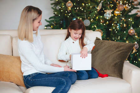 Cute girl daughter giving Christmas gift her young smiling mother, sitting in room with decorated tree, happy family mom and child wearing white knitted sweaters celebrating New Year at home