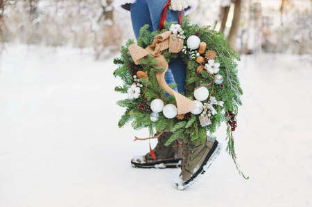 Unrecognizable female in outerwear carrying decorated Christmas wreath and standing on snow on sunny winter day