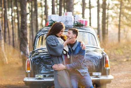 Side view of adult boyfriend and joyful woman in warm clothes embracing and looking at each other with love against black retro car in autumn forest at sunset