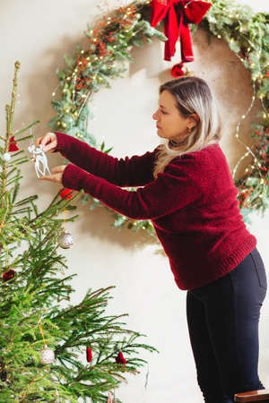 Side view of adult woman in red sweater hanging decorations on branches of coniferous tree on Christmas day at home