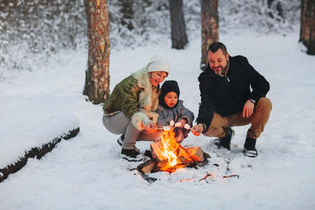Cheerful parents and son enjoying hot drink while resting near campfire in evening in winter forest Stockfoto