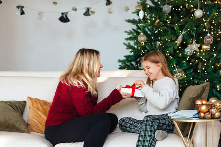 Joyful grandmother and lovely little girl in cozy knitted sweaters by Christmasmas fir tree with new year gift in living room, smile feeling atmosphere of winter holiday. Family holidays