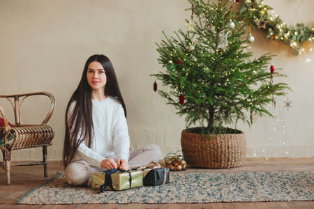 Beautiful brunette lady with long straight hair decorating Christmas Tree at home, raising hands holding festive presents, fairy lights and golden stars on fir-tree in living room