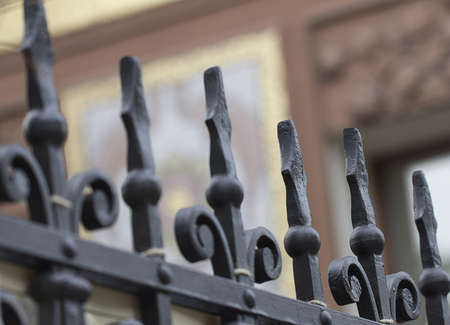 Fragment of black cast-iron fence at cloudy day