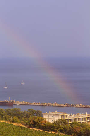 Rainbow over sea at sunny summer day photo