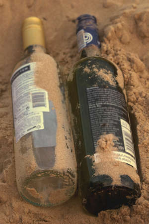 Picnic on beach with bottles of red and white wine in sand photo