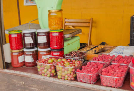 Jam and berries at village market in summer day
