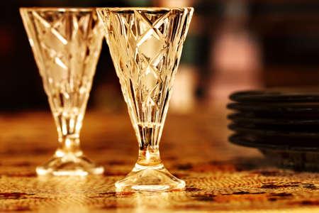 shot glasses: Two nice vodka shot glasses on table in golden colors