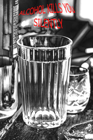hopelessness: Empty faceted glass closeup in black and white tones and with words about alcohol