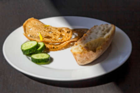 dieta: Dry bread and slices of fresh cucumber on white plate illuminated by sun Stock Photo