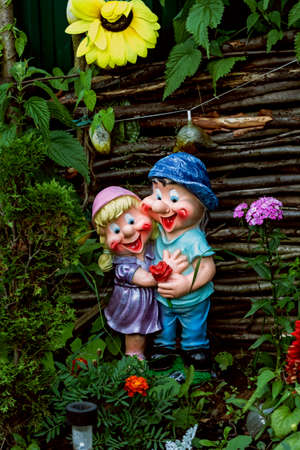 lawn gnome: Nice decorative figurines of jolly fellows couple in summer garden