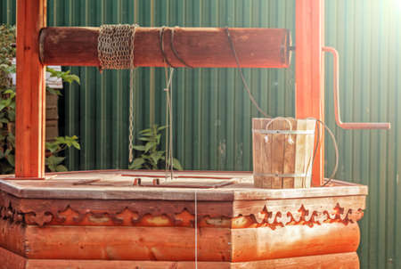 vertical wellness: Wooden bucket and well at sunny summer day Stock Photo