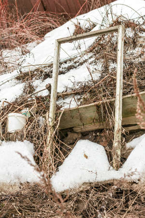 Old abandoned wooden window frame on snow