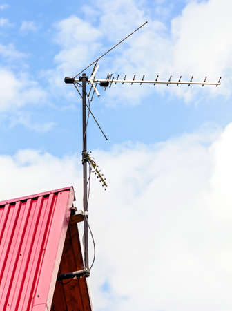 Antenna on red roof at sunny day in blue sky background