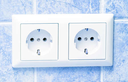sockets: Two white sockets in light blue wall Stock Photo