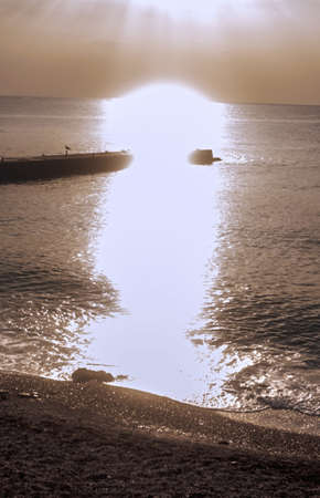 dazzle: Bright rays of sun dazzle on sea in sepia