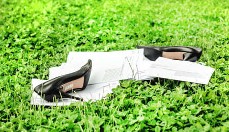 tied down: Down with office work, go on nature, shoes and green grass with paper at summer day