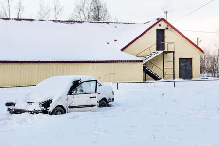 abandoned car: Abandoned car in snow near abandoned houses