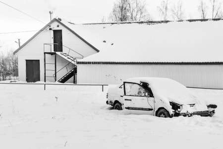 abandoned car: Abandoned car in snow near abandoned houses in black and white