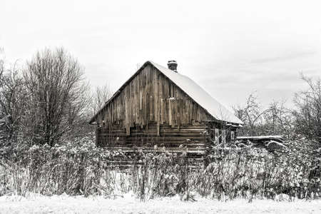 Big abandoned wooden house in snow of winter at sepia Stock Photo