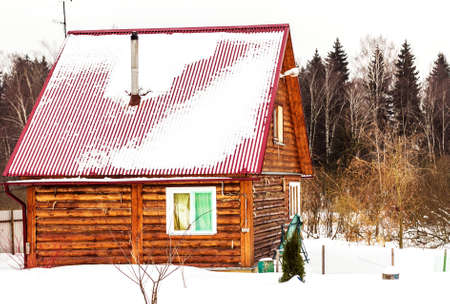 Wooden country cabin in snow at winter cloudy day