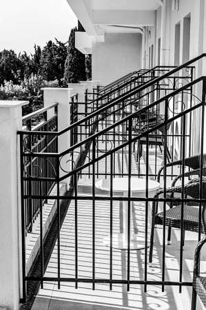 Balconies with tables and chairs at best sunny weather in black and white