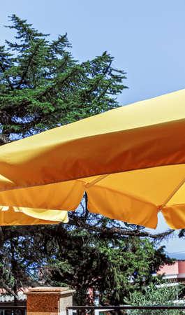 Yellow awning sun umbrella at happy bright weather